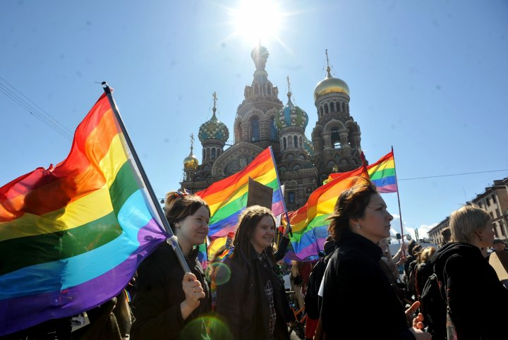 Large group of LGBT activists carry rainbow flags during parade in Russia.