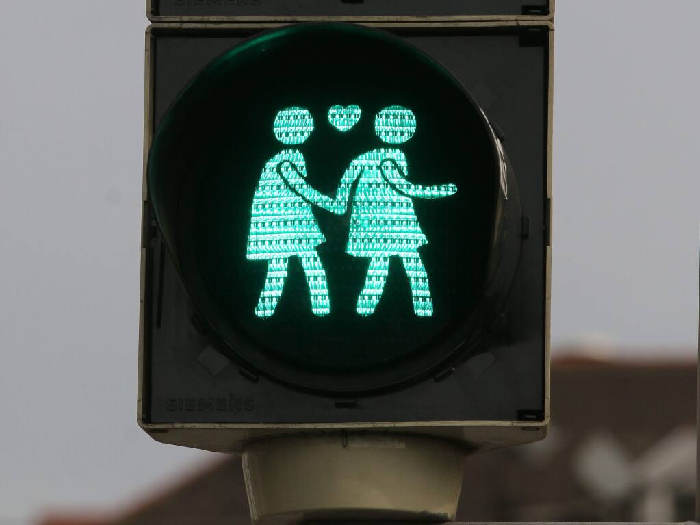 Image: Traffic Signal Vienna, Austria Press Democrat. Traffic signal shows two blue figures in dresses holding hands with a heart between them.