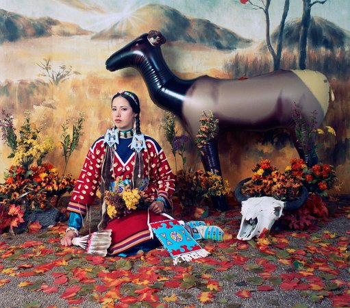 image of Wendy Red Star, a person indigenous to Turtle Island, pictured in a satirical portrait.  Wendy is wearing a Halloween native american costume and is surrounded by an inflatable deer in front of an artificial background of a prairie.