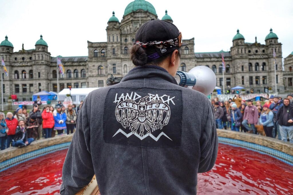 """photo shows the back of a person standing in front of an outdoor fountain filled with red water. the person is holding a megaphone and wearing a jacket with a patch that reads """"land back"""" and has a bird symbol.  the fountain is surrounded by people."""